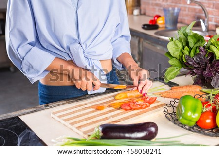 woman slicing carrot on kitchen board - stock photo