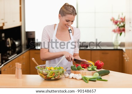 Woman slicing vegetables in her kitchen - stock photo