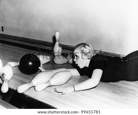 Woman sliding down bowling alley with ball - stock photo
