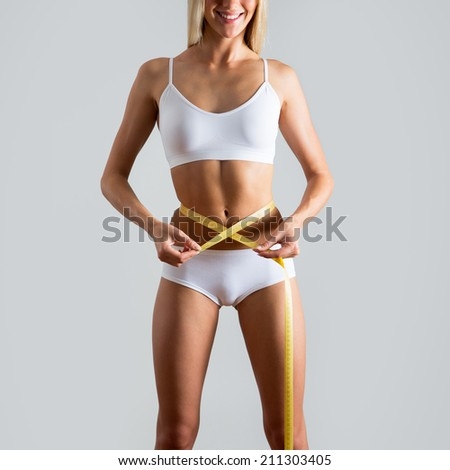 Woman slim body with yellow measure - stock photo