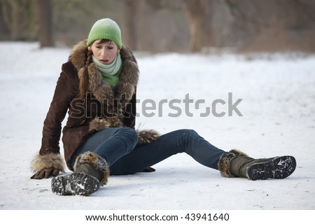woman slips and falls down on snowy road - stock photo