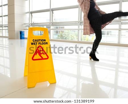 Woman slips next to wet floor sign - stock photo