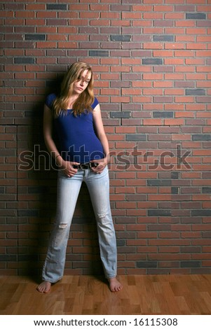 woman slouching hopelessly against brick wall - stock photo