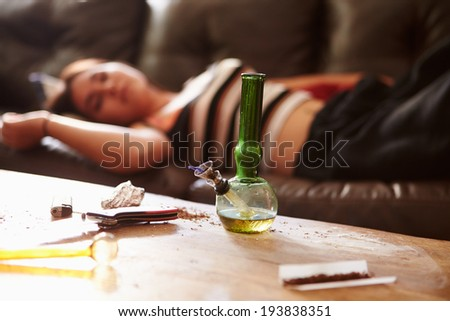 Woman Slumped On Sofa With Drug Paraphernalia In Foreground - stock photo