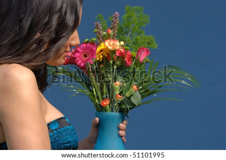 woman smelling a bouquet of summer flowers