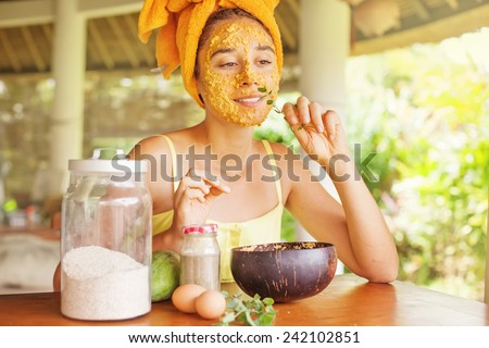 woman smelling a mint leave while doing face mask at home - stock photo