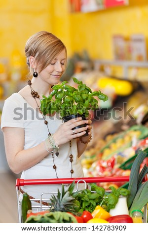 Woman smelling a potted fresh basil plant in a supermarket with a blissful smile as she stands with a trolley full of fresh groceries - stock photo