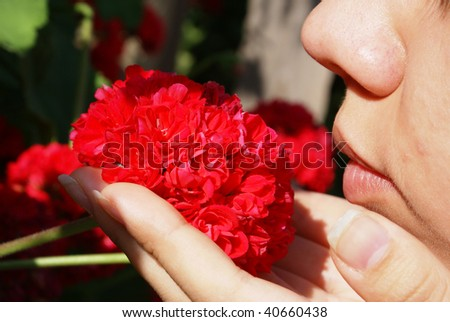 Woman smelling a small wildflowers bouquet - closeup - stock photo