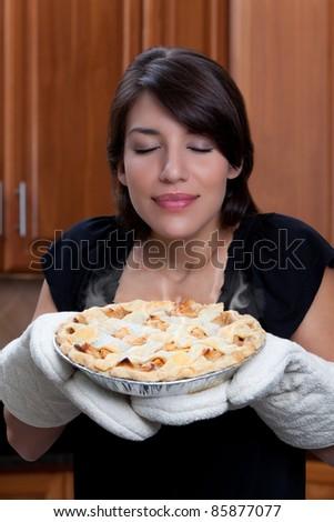 Woman smelling apple pie - stock photo