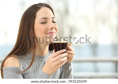 Woman smelling coffee aroma in a transparent cup in a terrace with the sea in the background - stock photo