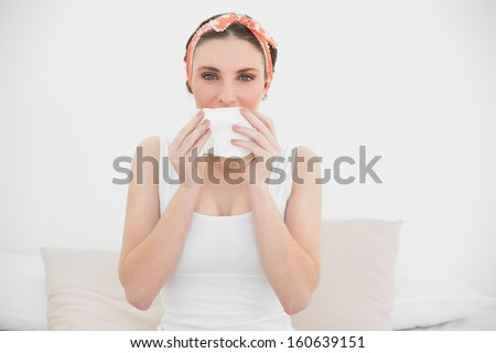 Woman smelling on a handkerchief looking into the camera sitting on her bed - stock photo