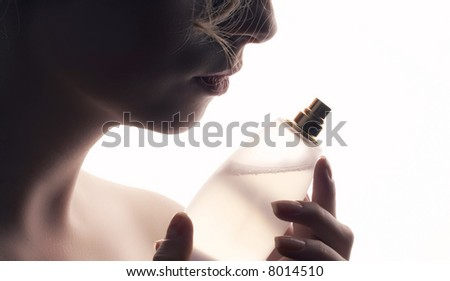 woman smelling perfume - stock photo