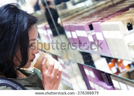 woman smelling the scented candle at shop, Paris. Customer tries goods in the store. Asian woman sniffs scented candle. Portrait of woman in shop testing perfume goods. Woman chooses aroma of candle. - stock photo