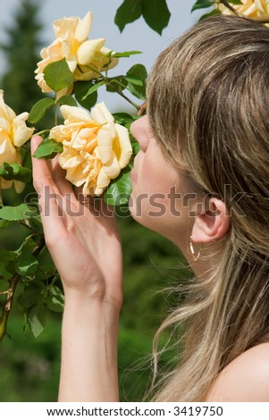 Woman smelling the yellow roses - stock photo