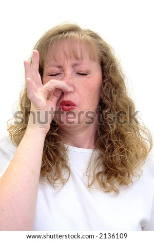 Woman smells something really bad and is pinching her nose in disgust.  Isolated on white. - stock photo