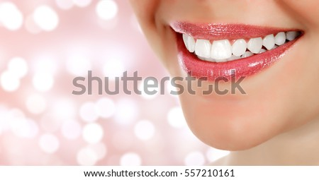 Woman smile closeup against an abstract background with blurred lights