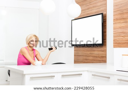 woman smile watching tv hold remote control changing channel, young girl in living room at home, isolated screen empty copy space - stock photo