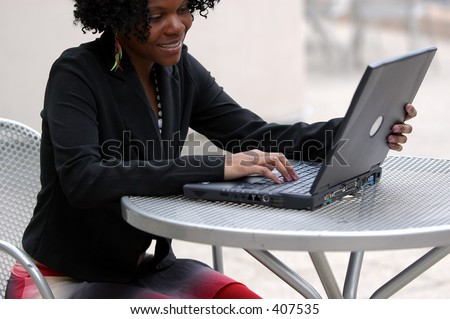 Woman smiles as she looks at the computer. - stock photo