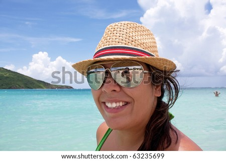 Woman smiles in the tropical Caribbean ocean on the  island of Culebra. Man taking her photo is shown in the reflection of her sunglasses.
