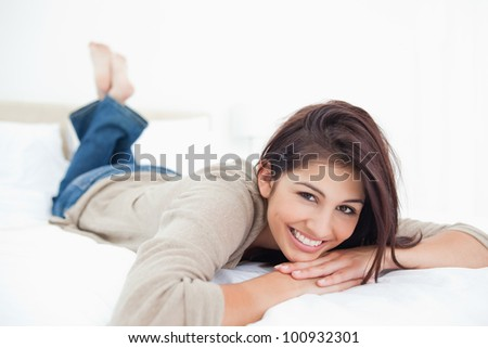 Woman smiles on the bed with crossed feet and her head being propped up by her hands. - stock photo