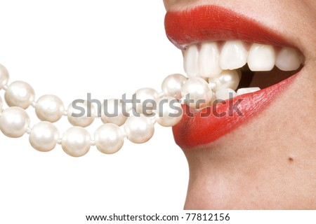 woman smiles showing white teeth, holding a pearly necklace in to the mouth, teeth care concept - stock photo