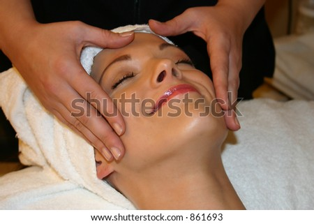 Woman Smiles While receiving Facial Massage - stock photo