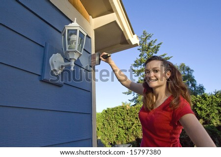 Woman smiles with her hand on her hip as she paints her house. Horizontally framed photograph. - stock photo