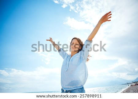 woman smiling  against blue sky looking at the camera
