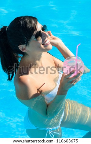 Woman smiling and drinking a cocktail in swimming pool a hot summer day. She wears white bikini and sunglasses.