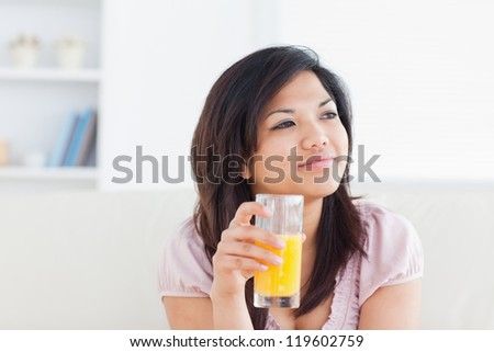 Woman smiling and holding a glass of orange juice in a living room - stock photo