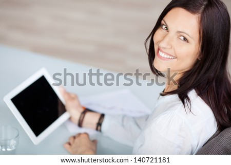 Woman smiling and holding a tablet in an aerial view - stock photo