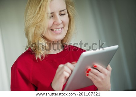 Woman smiling and looking at ipad - tablet - stock photo