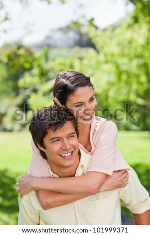 Woman smiling and looking to her side as her friend is carrying her on his back