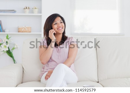 Woman smiling and phoning in a living room - stock photo