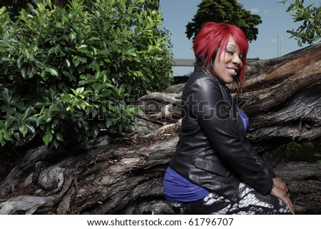 Woman smiling and squatting in a nature setting - stock photo