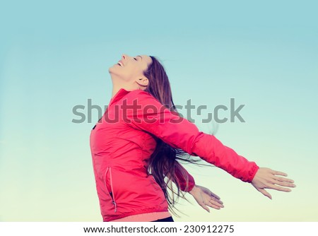 Woman smiling arms raised looking at blue sky taking deep breath celebrating freedom. Positive human emotion face expression feeling life perception success peace mind concept. Free girl enjoy nature - stock photo