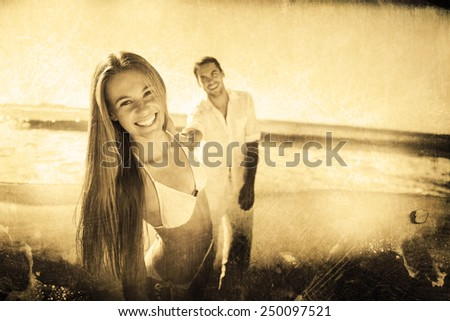 Woman smiling at camera with boyfriend holding her hand against grey background - stock photo