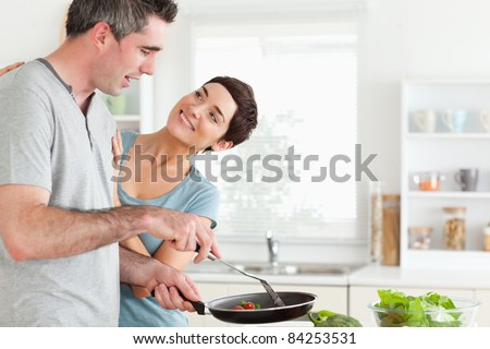 Woman smiling at her pan-holding husband in a kitchen - stock photo