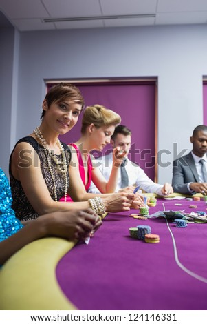 Woman smiling at the casino sitting at the poker table - stock photo
