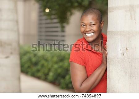 Woman smiling from behind a tree - stock photo