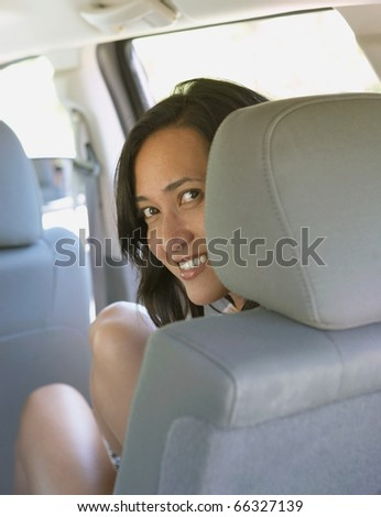 Woman smiling from SUV passenger seat - stock photo