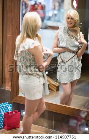 Woman smiling in a boutique while standing in front of a mirror - stock photo
