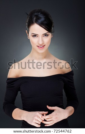 woman smiling in black isolated over a dark background - stock photo