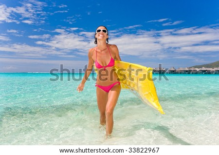 woman smiling on tropical beach on vacation - stock photo