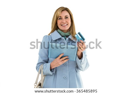 Woman smiling using her tablet and showing her credit card - stock photo