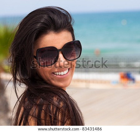 woman smiling wearing sunglasses in the beach - stock photo