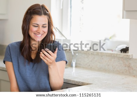 Woman smiling while calling her friend in the kitchen - stock photo