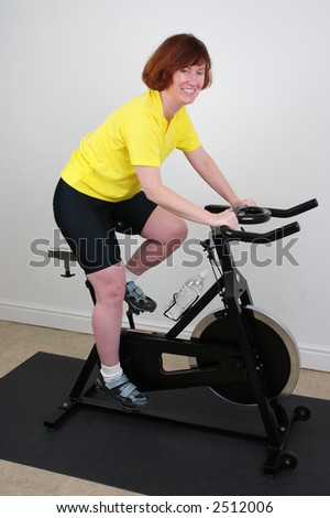 Woman smiling while exercising on a bike