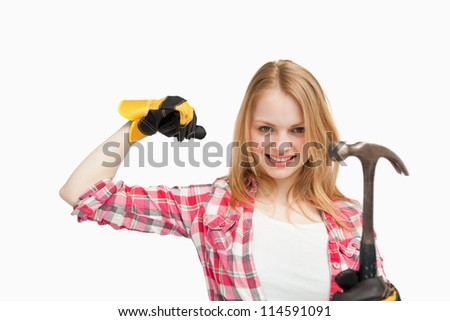Woman smiling while holding a hammer against white background - stock photo