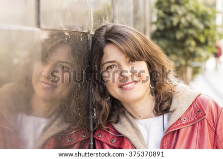 Woman smiling while leaning on wall outdoors - stock photo